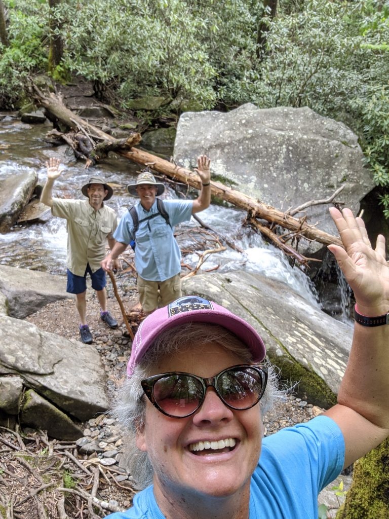 three handsome hikers at waterfall