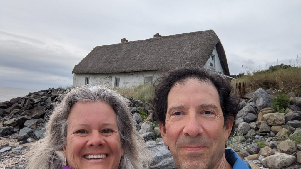 handsome couple in front of thatched hut